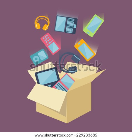Digital devices as laptop, desktop computer, mobile phones, headset and portable music players falling into an open card board box