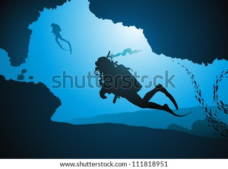 divers float among corals and