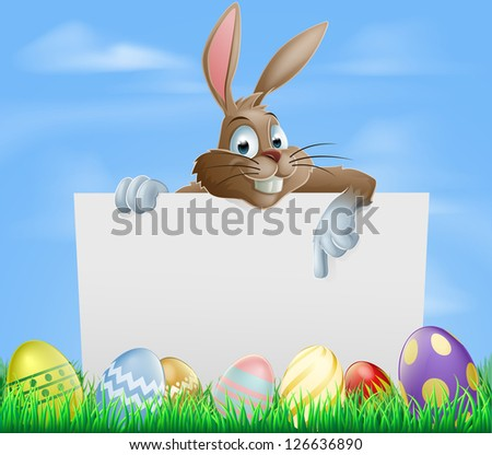 Easter bunny pointing at blank sign with painted chocolate Easter eggs in green field