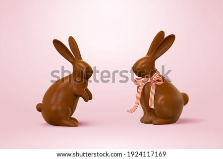 Easter chocolate rabbits, one with ribbon bow and one without. 3d holiday elements isolated on pink background.
