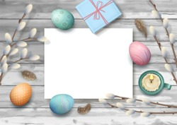 Easter holiday background with painted eggs, candle, gifts and a blank piece of paper on wooden background. Top view composition