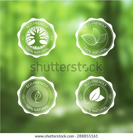Eco Vintage Labels Bio template set on blurred forest background. Ecology theme. Retro logo, icon, badge template designs with leaves and tree silhouette.
