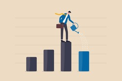 Economic recover from money stimulus, leadership to grow business, investment growth or profit and earning concept, businessman leader standing on profit bar graph watering this year growing bar chart