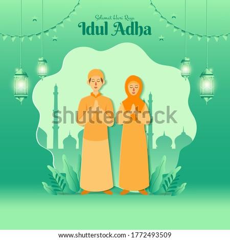 Eid al-Adha greeting card concept illustration in paper cut style with cartoon muslim couple blessing Eid al-Adha with mosque as background. Selamat hari raya Idul Adha translates to Eid al Adha