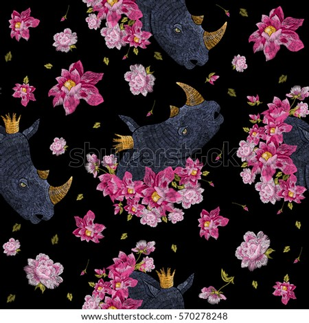 Embroidery colorful floral seamless pattern with fantasy rhinoceros. Vector trend folk flowers ornament on black background