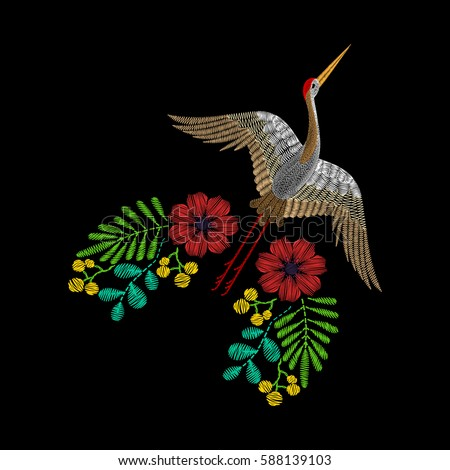 Embroidery with Asian crane, spring wildflowers for decor. Vector fashion embroidered ornament on black background for textile, fabric traditional folk decoration