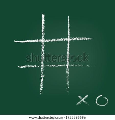 Empty cross zero game template handdrawn on green blackboard. XO handwritten sign on low corner. Tic-tac-toe competition. Chalk graffiti on board design. Entertainment and recreation. Grunge design Foto stock ©