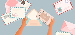 Envelopes and post cards on the table. Hands holding an envelope. Top down view. Greeting card and a letter in a hand. Modern vector illustration for web design and print. Retro cards and envelopes.