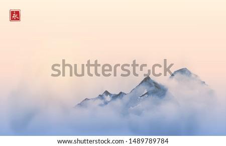 Far mountains over the dense fog and sunrise. Traditional oriental ink painting sumi-e, u-sin, go-hua. Hieroglyph - eternity