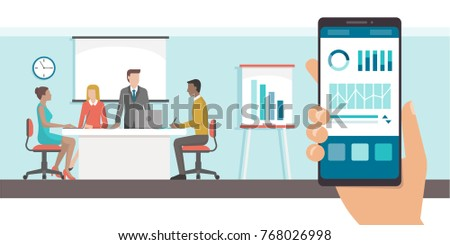 Finance and administration app with charts on a smartphone and business meeting in the office on the background