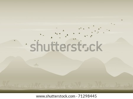 Flock of pigeons fly over mountain range.