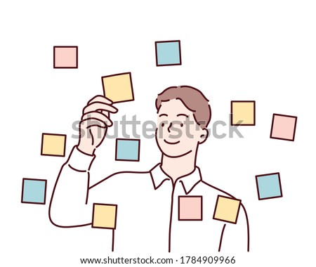 Focused young male employee writes ideas on sticky note on glass wall in office. Hand drawn style vector design illustrations.
