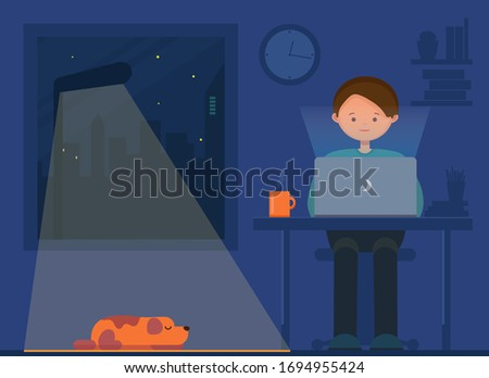 Freelancer working at night. Remote work. Young man and dog sitting in the room with laptop, surfing internet, networking. Programmer, designer, writer working at home. stock photo