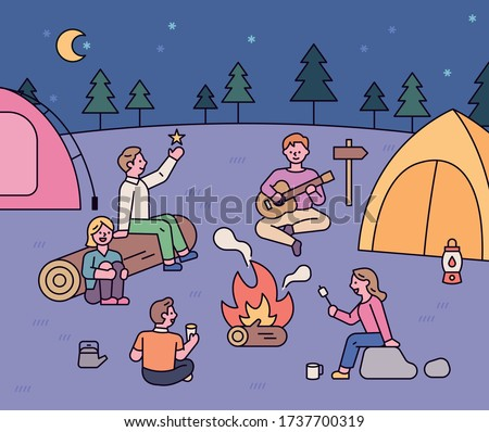 Friends sit around a campfire and have a romantic camping trip. flat design style minimal vector illustration.