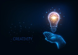 Futuristic glowing low polygonal light bulb and human hand isolated on dark blue background. Creativity, idea concept. Modern wire frame mesh design vector illustration.