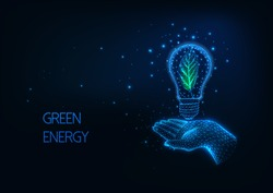 Futuristic green, renewable  energy concept with glowing low polygonal human hand holding light bulb with green leaf inside on dark blue background. Modern wire frame mesh design vector illustration.