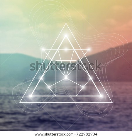 Futuristic vector art with interlocking hipster style triangles and other geometry shapes in front of blurry photo backdrop.