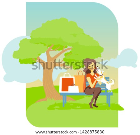 Girl sits in a park with her sweet dog