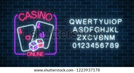 Glowing neon sign of online casino application in rectangle frame with alphabet on dark brick wall background. Casino bright signboard. Internet gambling banner. Vector illustration. #1223937178