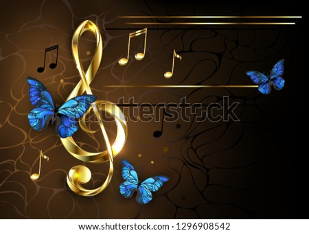 Golden musical key with gold shiny notes, decorated with blue butterflies on brown textured background.