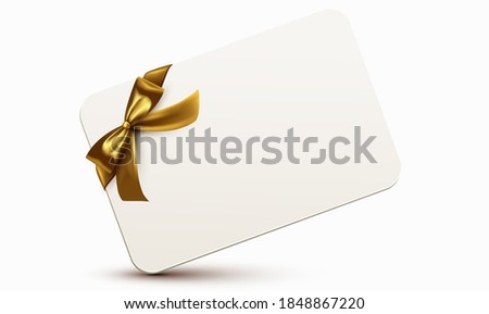 Golden ribbon with bow wrapped around a white rectangular card
