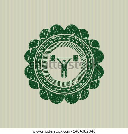 Green weightlifting icon inside distressed rubber stamp with grunge texture