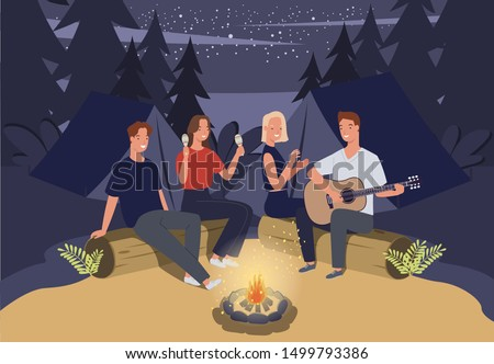 Group of friends camping. They are sitting around camp fire and playing guitar