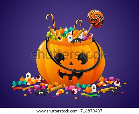 Halloween pumpkin basket full of candies and sweets on violet background