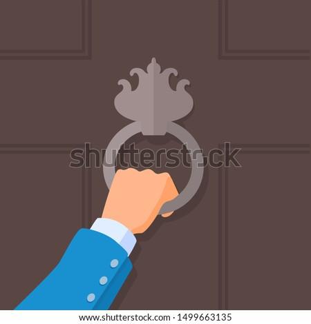 Hand holding a knocker on a door. Vector cartoon illustration.