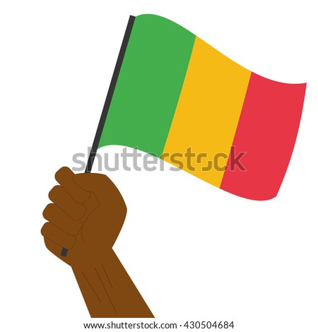 Hand holding and raising the national flag of Mali