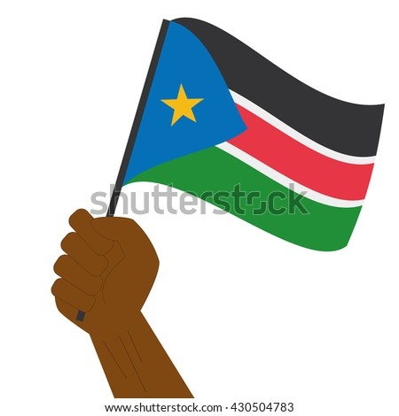 Hand holding and raising the national flag of South Sudan