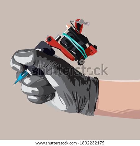Hand holding tattoo machine on light brown background. Tattoo artist holding tattoo machine.