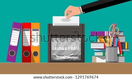 Hand putting document paper in shredder machine. Torn to shreds document. Contract termination concept. Table with books, stationery, ring binder. Vector illustration in flat design
