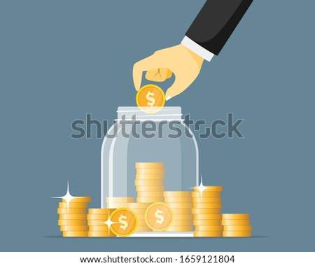hand saving coins in glass jar