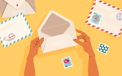 Hands holding an opened envelope. Envelopes, post stamps and post cards on the table. Top-down view.  Modern vector illustrated banner, card design. Correspondence and postal delivery concept.