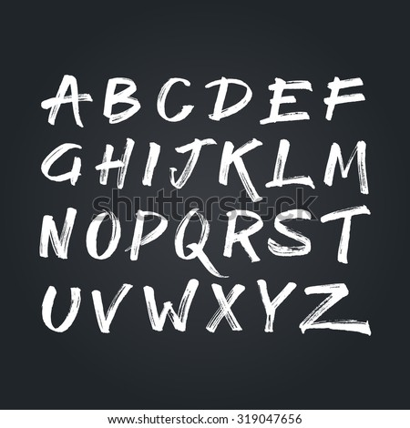 Handwritten calligraphic white alphabet written with brush pen on black chalkboard background. Handmade abc font typography