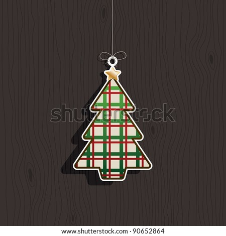 hanging christmas tree decoration on dark wood background