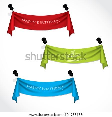 Happy birthday ribbons hanging on push pins