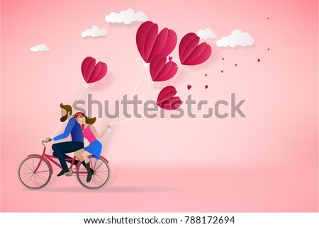 Happy couple is riding a bicycle together  and holding red balloons on pink  background.  Illustration of Love and Valentine Day. Paper cut style.