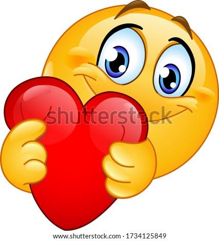 Happy emoji emoticon hugging a red heart