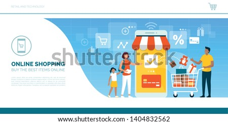 Happy family doing grocery shopping online with a mobile app on their smartphone, the man is holding a shopping cart with products and the woman is making the payment with a credit card