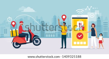 Happy family standing next to their smartphone in the city street, they are receiving a ready fast food meal ordered online using a mobile app, the delivery man is riding a moped