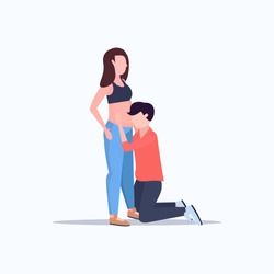 happy husband on knee listening his pregnant wife's belly cheerful couple man woman waiting newborn baby pregnancy parenthood concept full length