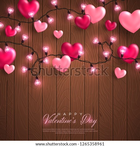 Happy Saint Valentine's day card with pink hearts and light garland on brown wood background.