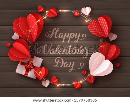 Happy Valentines day greeting card. Decorative paper cut hearts, gift box, garland with handwritten lettering text on brown wooden background. Vector illustration.