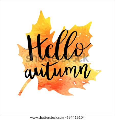 Hello autumn hand lettering phrase on orange watercolor maple leaf background