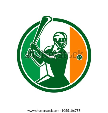 Icon retro style illustration of athlete or player playing Hurling, a Gaelic Irish sport,  striking sliothar ball with hurley wooden stick viewed from side set inside circle with Ireland Irish flag.