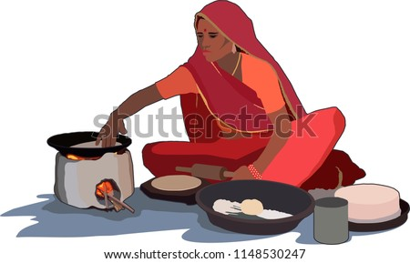 Indian village woman cooking food with traditional way of baking chapati on wood fire stove (chulha)