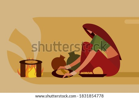 Indian woman making 'Roti' in traditional way on a fire stove