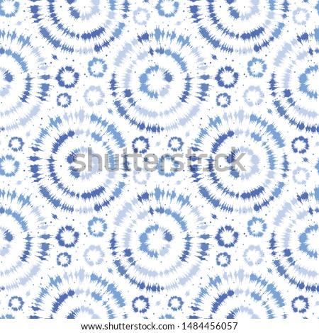 Indigo blue shibori tie dye sunburst circle background. Seamless pattern on white background. Japanese style batik textile. Variegated for summer fashion swatch.